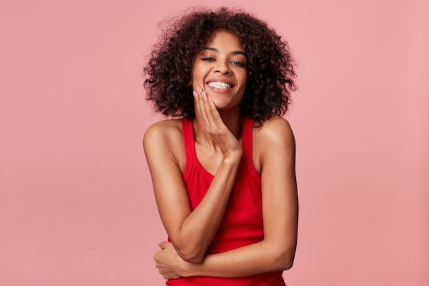 Happy pleased charming african american girl with afro hairstyle looks with pleasure, touches her face with palm, smiles, rejoices from soft skin, wearing red singlet, isolated