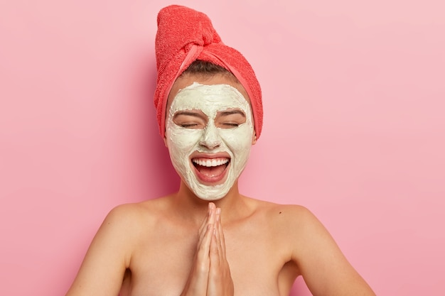 Happy pleased female keeps palms in praying gesture, smiles broadly, wears facial mask for rejuvenation, has fun at home, poses naked with bare shoulders, isolated on pink wall