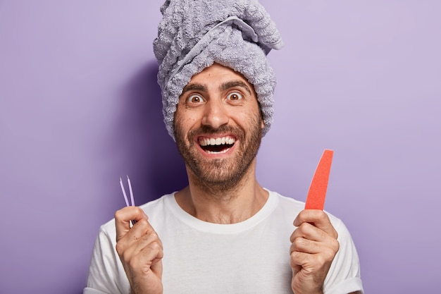 Happy pleased man with bristle holds nail file and tweezers, going to have beauty treatments in salon or at home, does nail up correction, has towel on head. spa