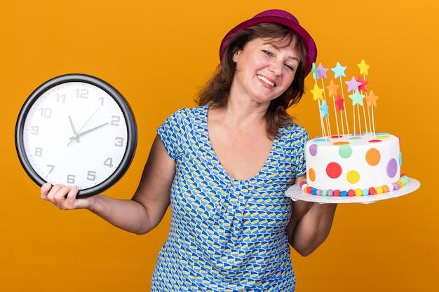 Felice e compiaciuta donna di mezza età con cappello da festa che tiene in mano una torta di compleanno e un orologio da parete che sorride allegramente mentre celebra la festa di compleanno in piedi sul muro arancione