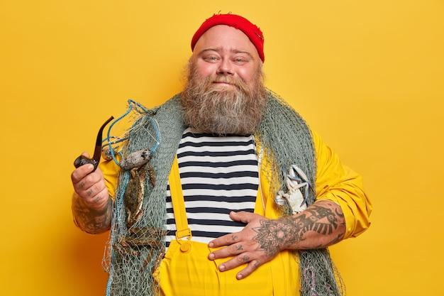 Felice marinaio contento tiene la mano sul grande stomaco, fuma la pipa e si gode la festa in spiaggia, posa con la rete da pesca