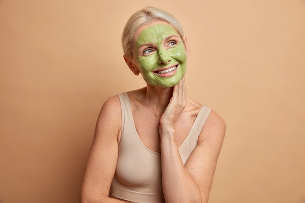 Happy pleased senior woman gets facial mask touches neck gently wears minimal makeup has dreamy face expression undergoes beauty treatments dressed in cropped top isolated over beige wall