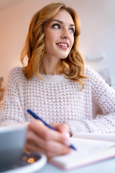 A happy pleased young blonde woman sit in cafe indoors writing notes in notebook.