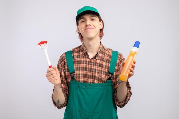 Felice e compiaciuto giovane uomo delle pulizie in camicia a quadri tuta e berretto che tiene spazzola per la pulizia e bottiglia con prodotti per la pulizia guardando davanti sorridente fiducioso in piedi sul muro bianco