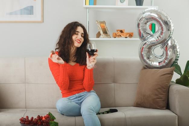 Felice e compiaciuta giovane donna in abiti casual sorridente allegramente seduta su un divano con un bicchiere di vino e cioccolatini nel soggiorno luminoso che celebra la giornata internazionale della donna l'8 marzo