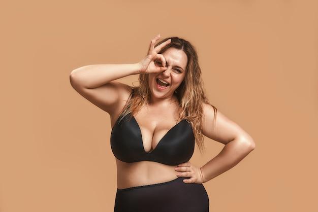 Счастливая пухлая женщина в черном нижнем белье показывает знак ок пальцами и подмигивает
