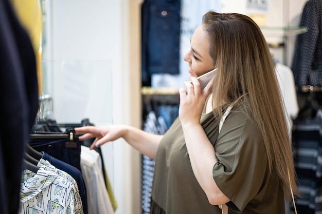 スマートフォンを話す店で服を選ぶ幸せなプラスサイズの美しい女性買い物中毒者