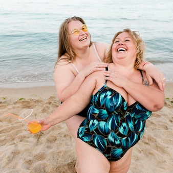 Felici amici taglie forti in spiaggia