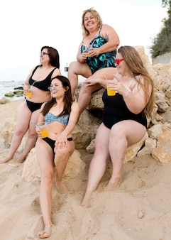 Happy plus size friends sitting on rocks together