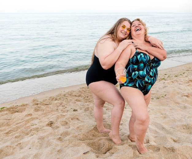 Happy plus size friends standing in the sand