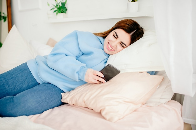 Happy plus size model in jeans and blue sweater, holding the phone in her hands, is lying on the bed smiling. fashion. communication