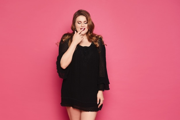 Happy plus size model woman with red lips in a short black dress against the pink background, isolated.