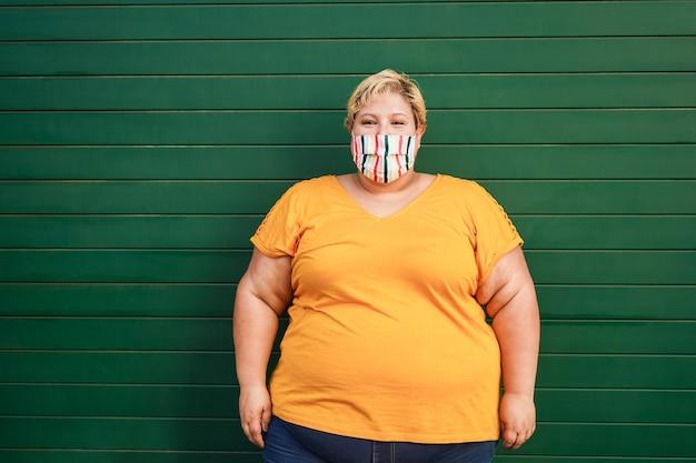 Счастливая женщина больших размеров в защитной маске во время вспышки коронавируса