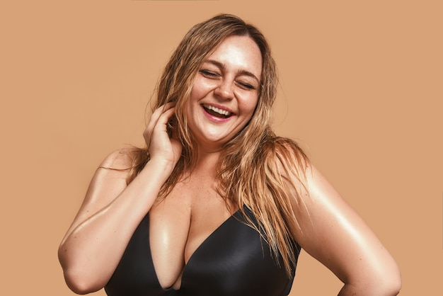Счастливый плюс размер молодая женщина в черном белье смеется и позирует в студии на коричневом