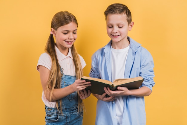 Happy portrait of boy and girl reading the book standing against yellow background