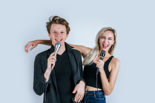 Happy portrait of couple holding microphone and sing a song