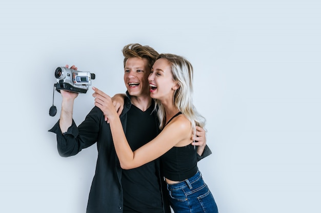 Happy portrait of couple holding video camera and record clip video