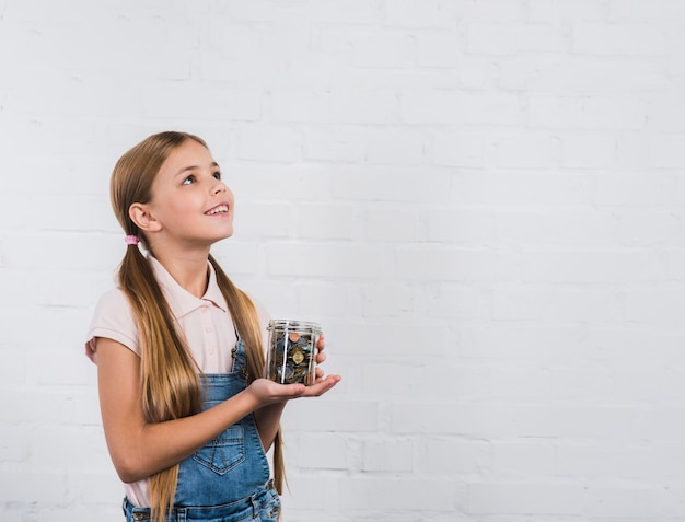 Happy portrait of a girl holding piggybank standing against white brick wall looking up