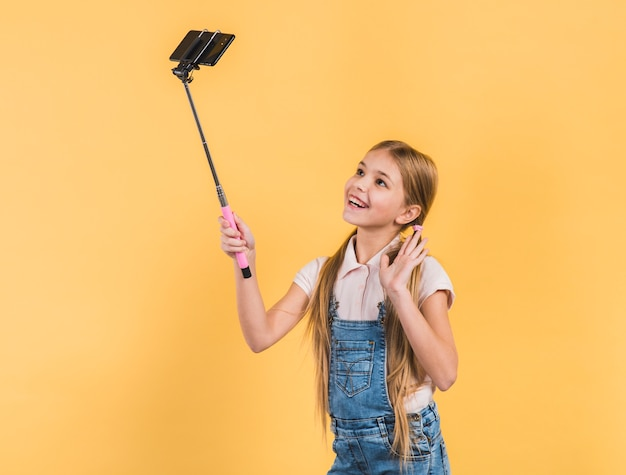 Happy portrait of a girl waving her hand taking selfie on mobile phone against yellow background