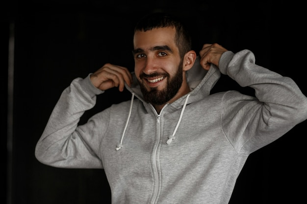 Happy portrait of a handsome young man with a beard in a gray hoodie on a dark wall