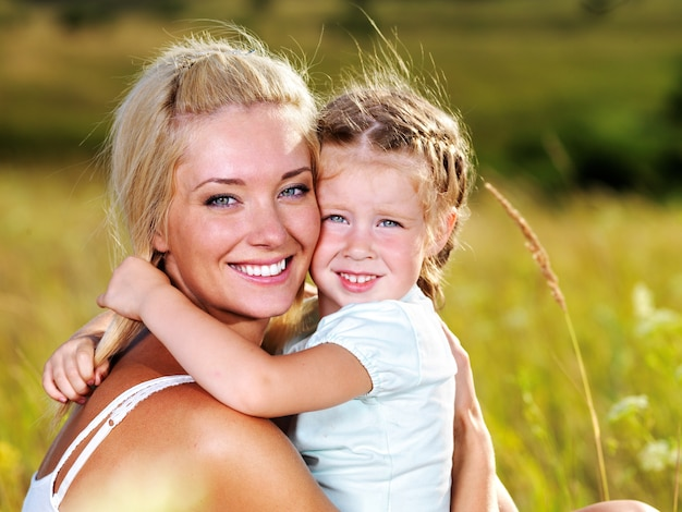 Happy portrait of the mother and little daughter outdoors
