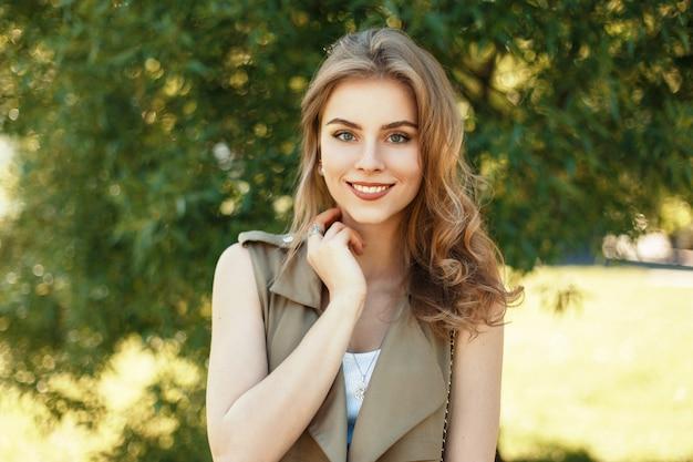 Счастливый портрет красивой веселой женщины с милой улыбкой возле дерева в солнечный весенний день