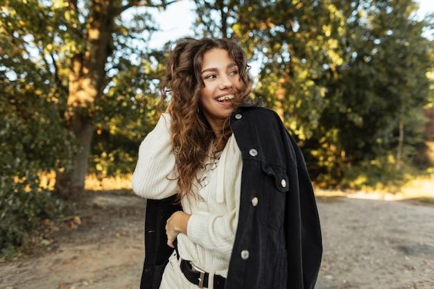 세련된 검은색 청바지 재킷과 니트 블라우스를 입은 곱슬머리를 한 아름다운 소녀의 행복한 초상화는 자연 속을 걷습니다. 여성 웃는 얼굴
