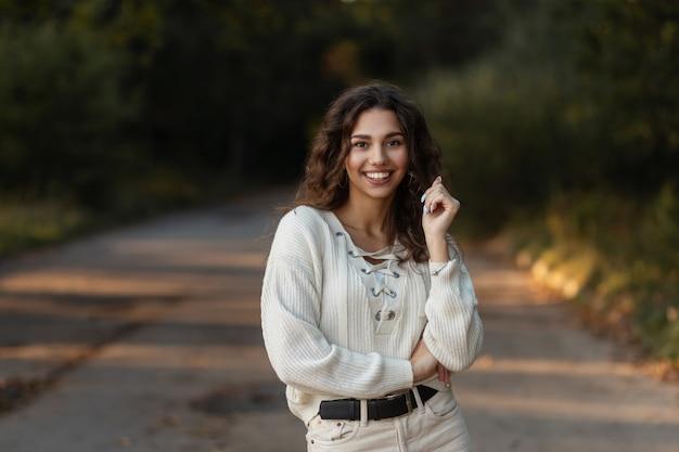 미소를 가진 꽤 곱슬곱슬한 젊은 여성의 행복한 초상화는 자연 속을 걷고 카메라를 쳐다본다