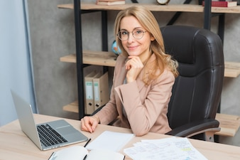 Happy portrait of a smiling young businesswoman sitting on chair at workplace with laptop and papers on table