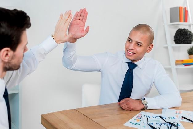 Счастливый портрет молодого бизнесмена, давая высокие пять его деловому партнеру в офисе