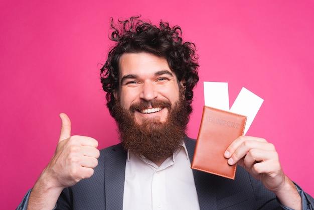 Счастливый портрет красивого бородатого мужчины в непринужденной обстановке показывает большой палец вверх и проездные билеты с паспортом