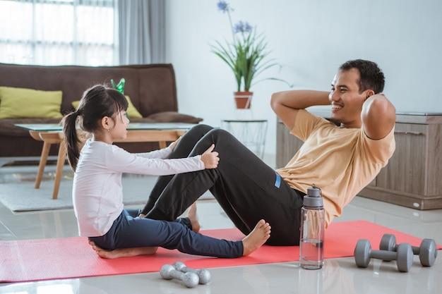 Счастливый портрет ребенка, помогающего своему отцу делать сидячие упражнения дома
