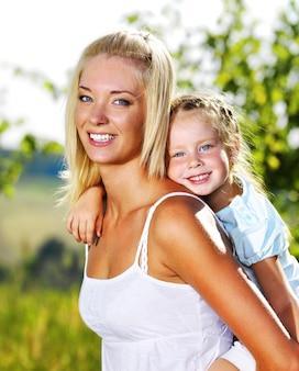 Счастливый портрет матери и маленькой дочери на открытом воздухе