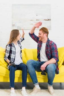 ゲームコンソールをプレイした後お互いに高い5つのジェスチャーを与える若いカップルの幸せな肖像画