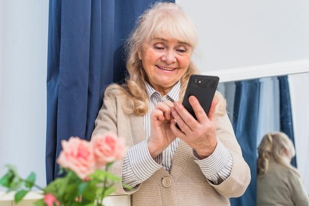 Happy portrait of a senior woman using mobile phone