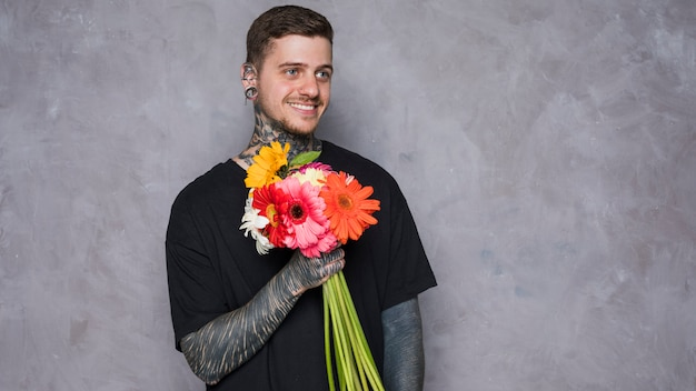 Happy portrait of a smiling man with tattoo on his hand holding gerbera flower against wall