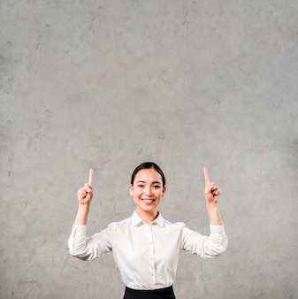 Happy portrait of a smiling young businesswoman pointing her fingers upward against grey wall