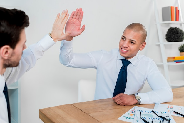 Happy portrait of a young businessman giving high-five to his business partner in the office