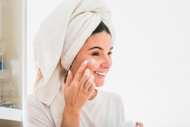 Happy portrait of a young woman applying cream on her face