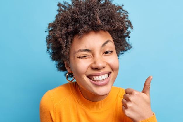 Счастливая позитивная афроамериканка широко улыбается, делает нормальный жест с поднятым вверх пальцем, говорит, что отлично подмигивает, глаза широко улыбается, носит оранжевый джемпер, одобряет что-то изолированное на синей стене
