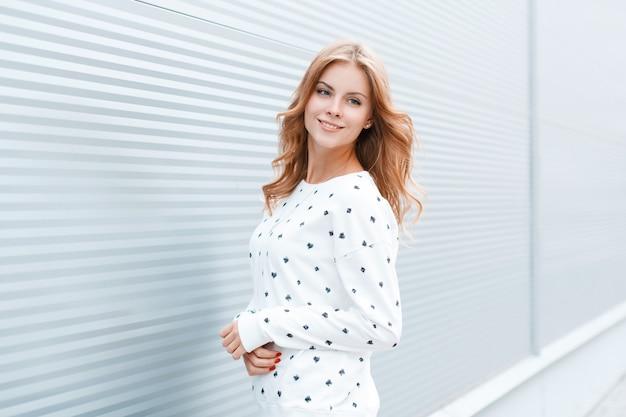 Счастливая позитивная привлекательная молодая женщина в модном белом свитере в городе возле яркой современной металлической стены в теплый весенний день