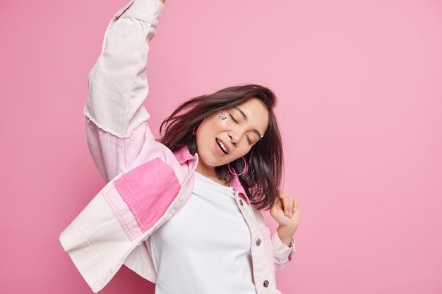 동부 외모와 함께 행복 긍정적 인 갈색 머리 편안한 여자는 팔을 올려 춤을 즐겁게 눈을 감고 레저 주말을 즐긴다. 분홍색 벽 위에 고립 된 세련된 옷을 입는다.