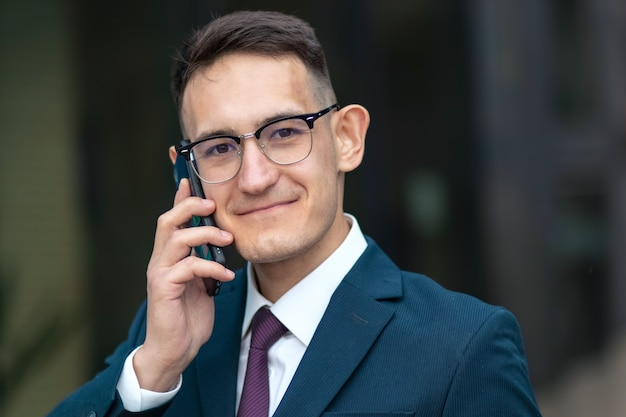 Счастливый позитивный бизнесмен разговаривает по телефону