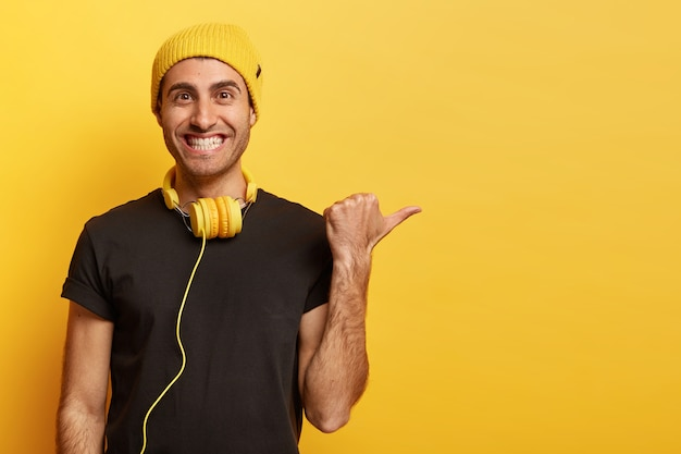 Счастливый позитивный кавказский мужчина с зубастой улыбкой, показывает пальцем на пустое место, продвигает товар