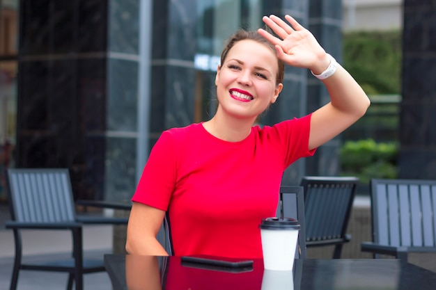 Happy positive cheerful girl young beautiful woman in red sitting in cafe, smiling, waving her hand and greeting friend, meet someone. cell mobile phone and coffee on table. good to see you! hello, hi
