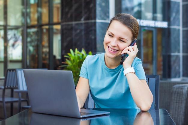 Счастливый позитивный веселая девушка, молодая занятая красивая женщина, улыбаясь, в чате, говорить на мобильный мобильный смартфон, глядя, набрав на своем ноутбуке, компьютер на открытом воздухе в кафе. концепция технологии и людей