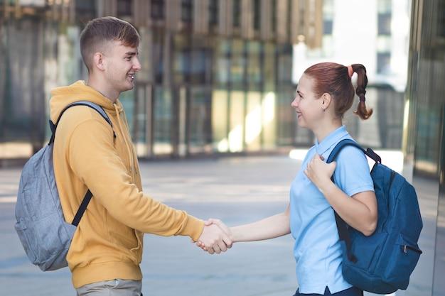 幸せな肯定的なカップル、2人の大学生が握手、バックパックで立って、笑顔。