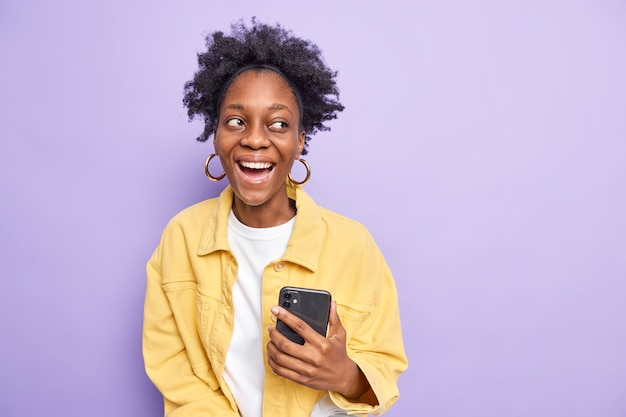 Happy positive curly teenage girl with dark skin holds smartphone looks pleasantly away dressed in yellow jacket uses modern technologies isolated on purple