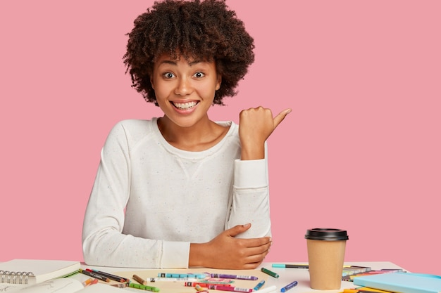 Happy positive dark skinned woman with afro hairstyle, points aside at free space for your advertisement or promotion, has joyful facial expression, enjoys creative work, models over pink wall