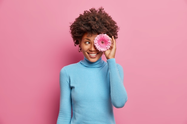 Happy positive dark skinned young woman covers eye with pink gerbera, has toothy smile, dressed casually, poses indoor, enjoys spring time.